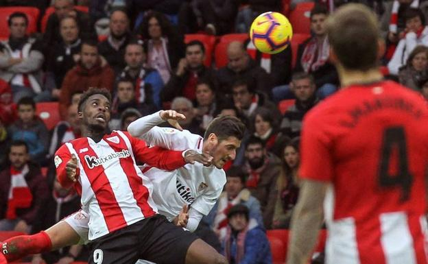 El delantero del Athletic Iñaki Williams pelea un balón con el defensa del Sevilla Sergio Escudero./