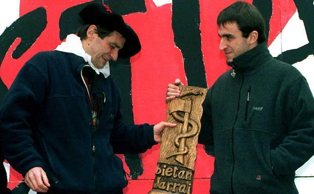 'Josu Ternera' recibe una talla con el hacha y la serpiente -similar a la del nuevo emblema de ETA- de manos de su hijo al salir de la cárcel en 2000./EL CORREO