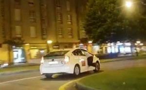 Colgado de la ventanilla de un taxi por las calles de Gijón