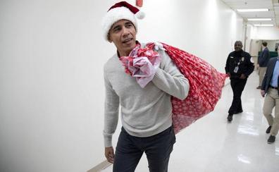 Obama entrega regalos a los niños enfermos vestido con el gorro y el saco de Papá Noel