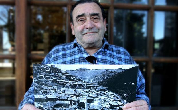 Pedro muestra una foto de un asentamiento chabolista.