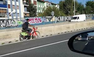 En bicicleta eléctrica municipal por mitad de la A-8 en Rekalde