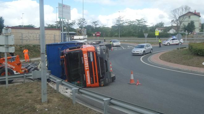 Un camión cargado de escombros vuelca en la rotonda de la subida a la UPV de Leioa